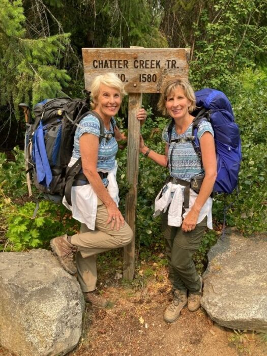 two women with backpacks at the Chatter Creek Trail signpost