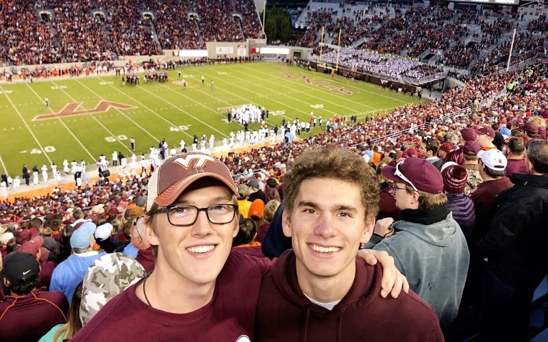 Two college guys at a Virginia Tech football game.