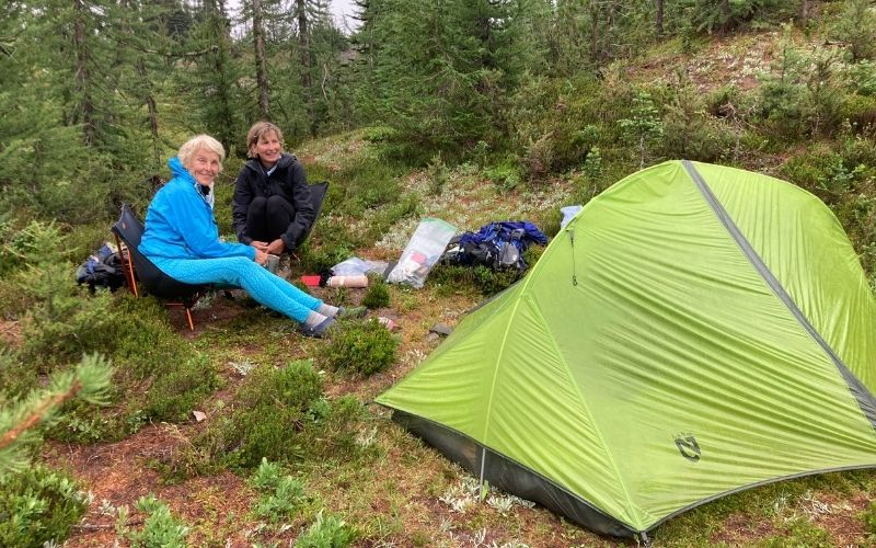 two women camping with green tent