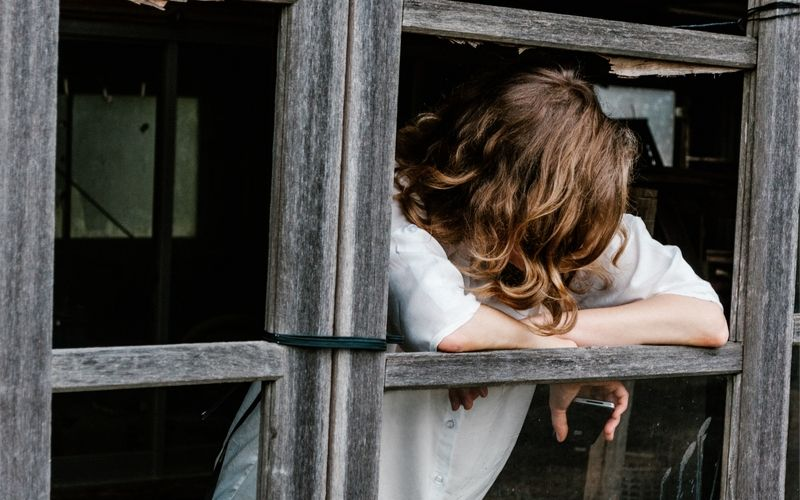 woman leaning out of open window in old barn, looking down