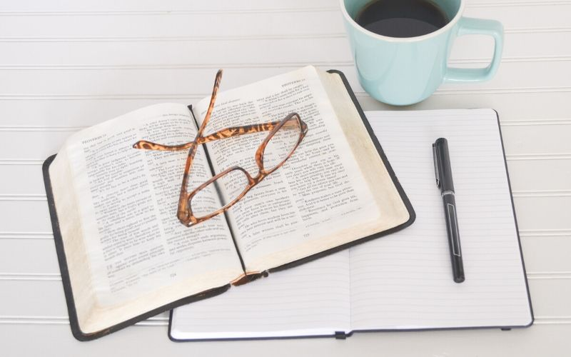 Bible with notebook, pen, glasses, and cup of coffee