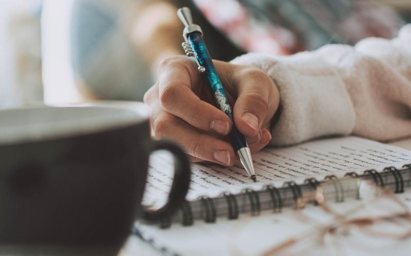woman journaling with a cup of coffee