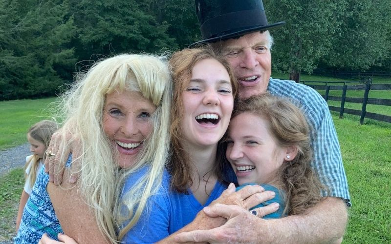 John and Susan Yates (in a top hat and wig) with two granddaughters.