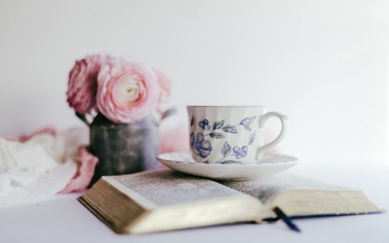 Open Bible with china teacup and saucer sitting on top, pink roses in background.