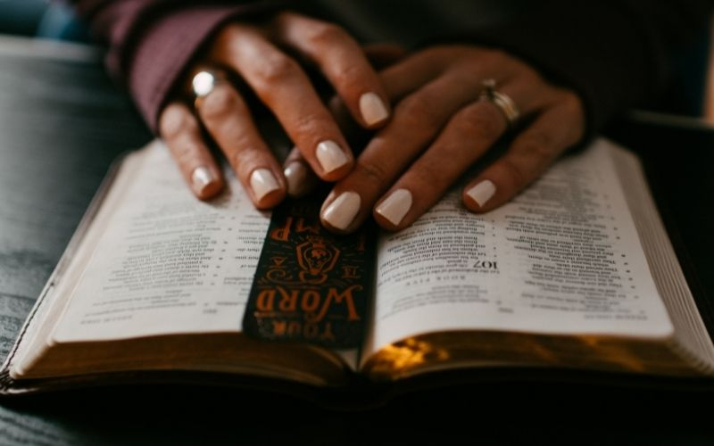 open Bible with a woman's hands on top