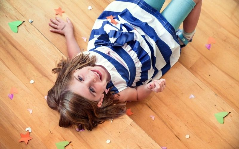 young girl on the floor, throwing paper confetti