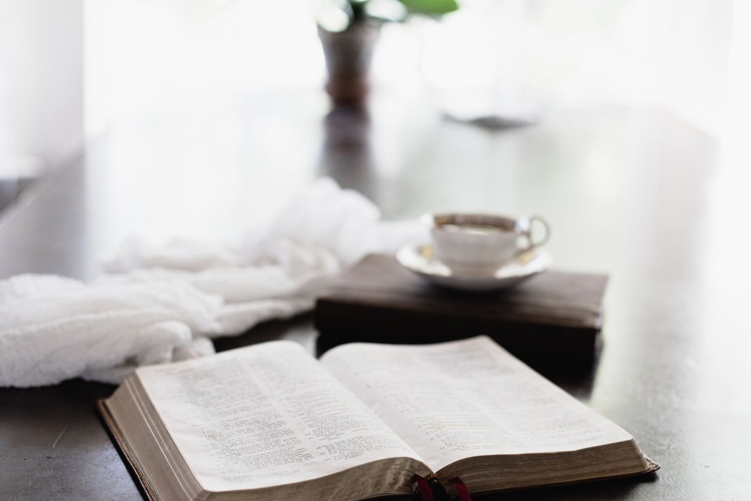 Bible, scarf and cup of coffee on dining room table