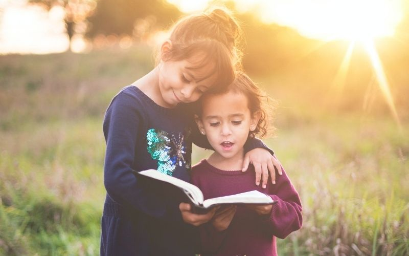 two small children in a field, reading a Bible