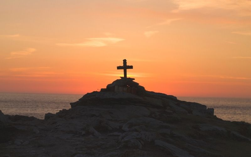 wooden cross on a rocky hill by the ocean at sunset