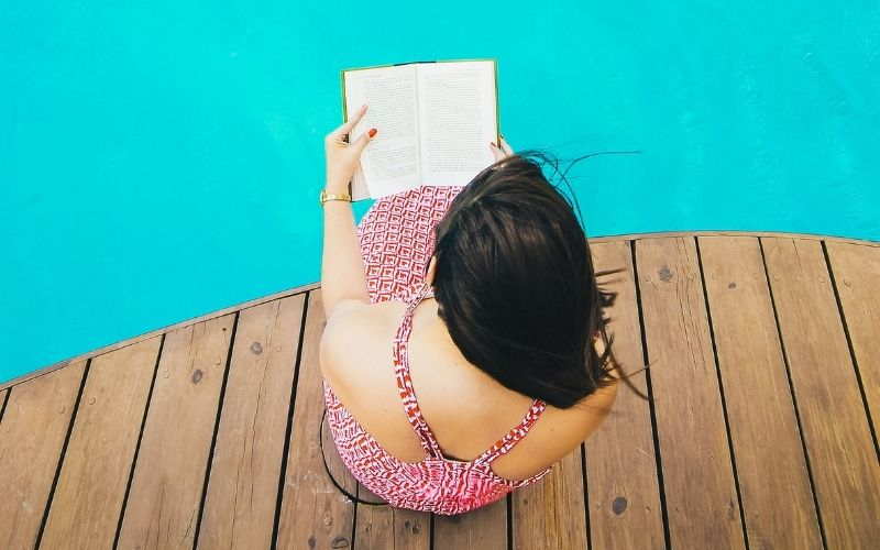 Woman sitting by a pool reading a book.