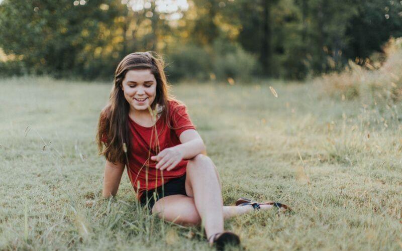 Teenage girl sitting in field.